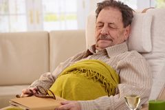 Senior man sleeping in armchair. Senior man lying in armchair, fell asleep while reading book Royalty Free Stock Photos