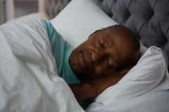 Senior man sleeping on bed Royalty Free Stock Images