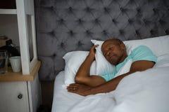 Senior man sleeping on bed at home. Senior man sleeping on bed in bedroom at home Royalty Free Stock Photography