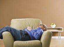 Senior man sleeping on chair. Royalty Free Stock Photos