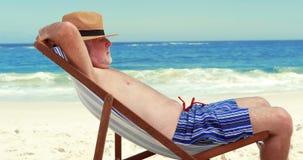Senior man sleeping on deck chair. At the beach stock footage