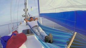 Senior man sleeping in hammock on sailing yacht, vacation, rest. Stock footage stock video
