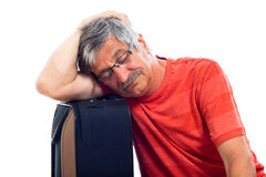 Senior man sleeping on luggage Stock Images