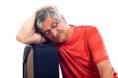 Senior man sleeping on luggage. Tired senior man sleeping on luggage, isolated on white background Stock Images