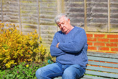 Senior man sleeping outside on a bench. Stock Images