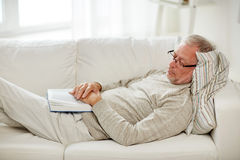 Senior man sleeping on sofa with book at home Royalty Free Stock Photography