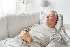 Senior man sleeping on sofa at home. Old age, rest, comfort and people concept - senior man sleeping on sofa at home Stock Photos