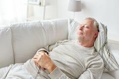Senior man sleeping on sofa at home Stock Photos