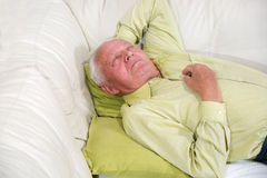 Senior man sleeping on sofa indoors Royalty Free Stock Photos