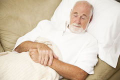 Senior Man Sleeps on Couch. Senior man sound asleep on the couch, suffering from a cold Royalty Free Stock Images