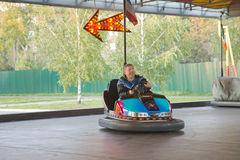 Senior man in small car at amusement park Royalty Free Stock Photos