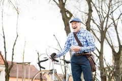 Senior man with smartphone and bicycle in town. Royalty Free Stock Image