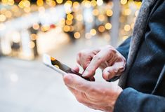 Senior man with smartphone in shopping centre at Christmas time. Stock Photo
