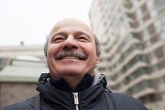 Senior man smiles and looks up Stock Photo
