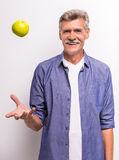 Senior man. Smiling senior man in casual throwing a green apple up and smiling while standing against grey background royalty free stock image