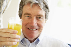 Senior Man Smiling And Drinking Orange Juice royalty free stock image