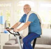 Senior man smiling on fitness bike Stock Photo