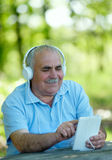Senior man smiling happily as he listens to music Stock Photos