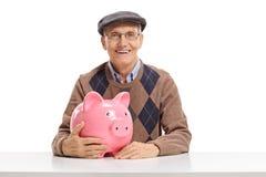 Senior man with a piggy bank royalty free stock photo