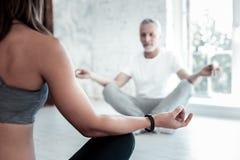 Senior man smiling while meditating during yoga class Royalty Free Stock Photo