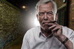 Senior man smoking a cigar Royalty Free Stock Images
