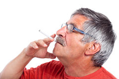 Senior man smoking cigarette Stock Photography