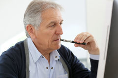 Senior man smoking electronical cigarette and working on computer Royalty Free Stock Image