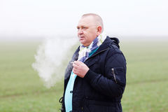 Senior man smoking over foggy field Royalty Free Stock Images