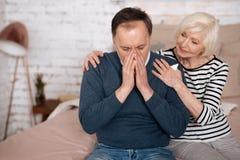 Senior man sneezing near wife Royalty Free Stock Photography