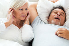 Senior man snoring and woman covering ears Stock Images