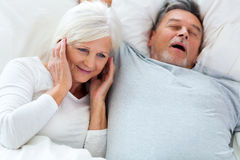 Senior man snoring and woman covering ears. Senior couple lying in bed together Stock Photography
