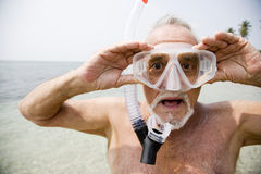 Senior man with snorkel gear at the beach Stock Images