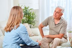 Senior man with social worker. Old aged senior men talking with social worker women at home Stock Image