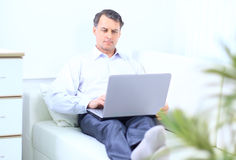 Senior man in sofa. With laptop computer Stock Image