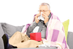 Senior man on a sofa blowing his nose in a handkerchief Royalty Free Stock Photography