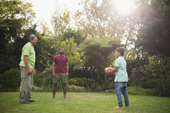 Senior man with son and grandson playing rugby at park stock photo
