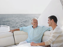 Senior Man With Son Relaxing On Yacht Stock Images