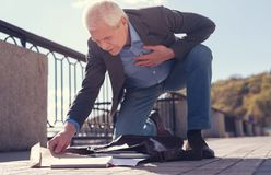 Senior man with sore heart gathering his scattered belongings. Feeling poorly. Handsome elderly man gathering his scattered belongings to a leather bag while Royalty Free Stock Photos