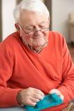 Senior Man Sorting Medication Using Organiser. At Home Royalty Free Stock Images