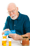 Senior Man Sorting Pills. Senior man uses a pill organizer to prepare his medication for the week.  White background Royalty Free Stock Photo