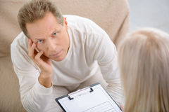 Senior man speaking with psychologist stock photography