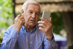 Senior Man Speaking by Video Call Outdoors. Portrait of senior businessman using video call by smartphone in outdoor cafe lounge Stock Images