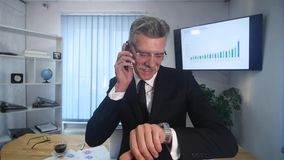 Senior man speaks with white smartphone in office stock video