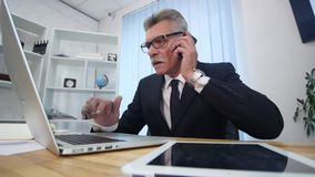 Senior man speaks with white smartphone in office Stock Photo