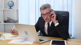 Senior man speaks with white smartphone in office Royalty Free Stock Photo