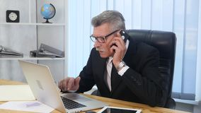 Senior man speaks with white smartphone in office.  Royalty Free Stock Photos