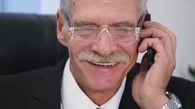 Senior man speaks with white smartphone in office. close up Stock Images