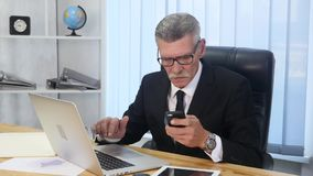 Senior man speaks with white smartphone in office Royalty Free Stock Images