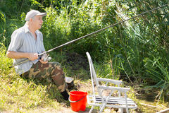 Senior man spending a relaxing day fishing Royalty Free Stock Images