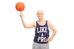 Senior man spinning a basketball on his finger. Senior man in a dark blue jersey spinning a basketball on his finger and looking at the camera isolated on white Royalty Free Stock Photos